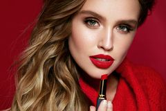 Red Lips. Beautiful Woman With Beauty Makeup Holding Lipstick. Close Up Of Young Glamorous Female Model With Bright Facial Makeup And Soft Fresh Healthy Skin stock photos