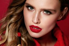 Red Lips. Beautiful Woman With Beauty Makeup Holding Lipstick. Close Up Of Young Glamorous Female Model With Bright Facial Makeup And Soft Fresh Healthy Skin royalty free stock image
