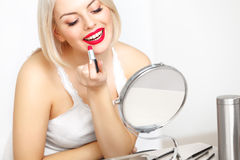Red lips. Beautiful Woman Doing Daily Makeup. Lipstick applying royalty free stock photo