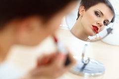 Red lips. Beautiful Woman Doing Daily Makeup. Stock Photo