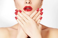 Red lips and bright manicured nails. Sexy open mouth. Beautiful manicure and makeup. Celebrate make up and clean skin Royalty Free Stock Photography