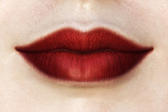 Red lips. Closeup of deep red female lips. Womens lips covered with dark red matte lipstick. Macro of lips with applied shocking red lipstick. Closed slightly royalty free stock photography