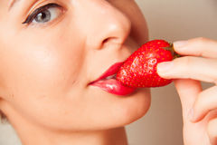 Red lips and delicious strawberry. Closeup portrait of woman lips holding strawberry Stock Photos