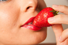 Red lips and delicious strawberry. Closeup portrait of woman lips holding strawberry Royalty Free Stock Photo