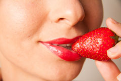 Red lips and delicious strawberry. Closeup portrait of woman lips holding strawberry Royalty Free Stock Photography