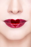 Red lips with heart shape. Beautiful sensual red lips with heart shape macro shooting. Professional make up. Red lipstick. Toned and clean skin. Happy Valentine Royalty Free Stock Images