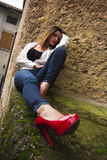 Red Lips & Heels. Beautiful model with red lips in red heels posing royalty free stock image