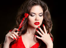 Red lips, manicured nails. Beautiful young woman model with beau Stock Photo
