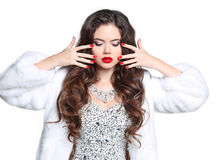 Red lips and manicured nails. Winter Brunette Woman in Luxury wh Royalty Free Stock Image