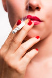 Red lips and red nails smoking cigarette V1 Royalty Free Stock Photography