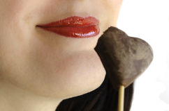 Red lips smiling with chocolate heart-shape cookie Stock Images