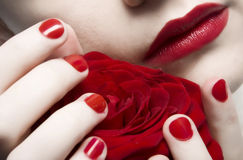 Red lips woman. Woman with red lips and nails holding rose Royalty Free Stock Photos