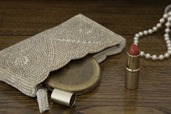 Red lipstick, 1920 pearl purse, compact and pearls. Open red lipstick in gold tube with 1920s pearl beaded purse containing vintage powder compact, a string of Royalty Free Stock Images