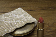 Red Lipstick with 1920 purse and vintage compact. Open tube of red lipstick in gold tube with 1920 pearl purse and vintage powder compact on antique oak dressing Royalty Free Stock Photo