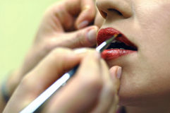 Red lipstick 6. Makeup artist applying a red lipstick Royalty Free Stock Photography