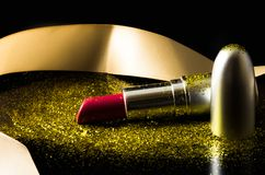 Red lipstick covered with golden specks of glitter dust on black background. Fancy and glamour photograph of a lipstick with ribbon and golden specks of glitter Royalty Free Stock Images