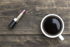 Red Lipstick and cup of coffee on wooden table Stock Image