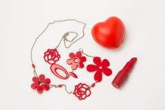 Red lipstick, heart and necklace with flowers on a white backgro Stock Photos