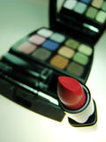 Red lipstick and makeup kit. In background Stock Image