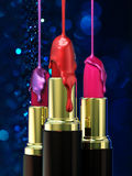 Red lipstick and multi-colored droplet nail polish on bokeh background. Stock Images