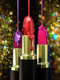 Red lipstick and multi-colored droplet nail polish on bokeh background. Royalty Free Stock Photography