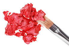 Red lipstick stroke (sample) with makeup brush. On white stock image