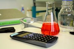 Red liquid in beaker on the table in laboratory Stock Photo