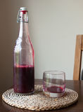 Red liquid glass bottle table fresh wild wine ruby Royalty Free Stock Image