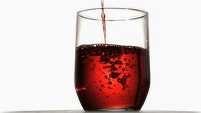Red liquid in super slow motion flowing in a glass. Against a white background stock video footage
