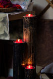 Red lit candles. Three red lit candles on a wooden holder Royalty Free Stock Image