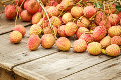 Red litchi on wooden floor Royalty Free Stock Photos
