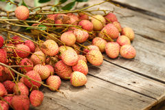 Red litchi on wooden floor Royalty Free Stock Image