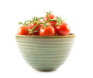 Red, little, cherry tomatoes in a green cup on a white background Royalty Free Stock Images