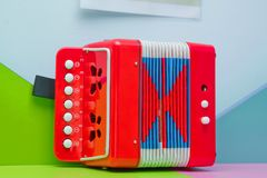 Red little Garmon for kids . A little accordion, harmonic, musical instrument, music repair white keys . musical instrument Garmon royalty free stock images