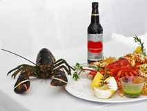 Red lobster with vegetables on a white plate. Isolated stock image