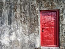 A red lock door on an old wall with some space for text. A red locked door fixed on an old rustic wall having texture royalty free stock photography