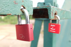 Red lock of love. The master key at green rail bridge Stock Image