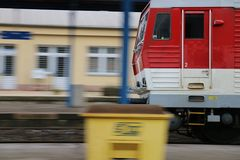 Red locomotive arriving to the station Royalty Free Stock Photos