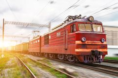 Red locomotive electric with a freight train at high speed rides by rail. Red locomotive electric with a freight train at high speed rides by rail royalty free stock image