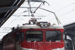 Red locomotive train in railway station in winter time Royalty Free Stock Images