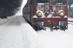 Red locomotive train in railway station in winter time Royalty Free Stock Photography