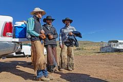 Three cowboys rest on their truck in Montana. RED LODGE, MONTANA, September 21, 2018 : A little rest for the cowboys after loading big trucks with cows, to stock photography