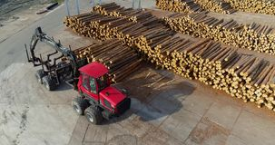 Red log truck, log truck, sawmill. A truck rides through the factory, a logger for transporting logs rides between the rows of logs stock footage