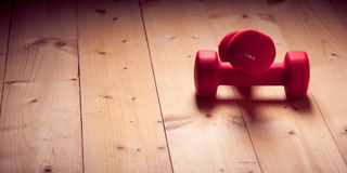 Red loght dumbbells on a wooden flor Stock Photography
