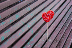 Red lollipop heart shaped on the bench. In park Royalty Free Stock Photography