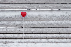 Red lollipop heart shaped on the bench. Red lollipop heart shaped on the snowy bench in winter park Stock Image