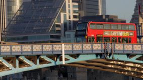 Red London Bus crossing Tower Bridge. Camera tracks a red London bus passing over Tower Bridge on a sunny autumn morning. Footage is 4K original stock video