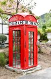 Red London phone booth in a garden. Red London phone booth in the garden Royalty Free Stock Photo