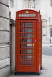 Red London telephone box, UK. London red telephone boxes against grey buildings in the background Stock Image