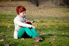 Red long hair girl at the park reading Royalty Free Stock Images